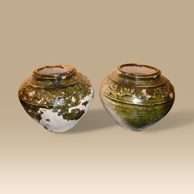 A pair of Han Dynasty 206 BC - 221 AD green glazed pots with a hunting scene depicted around the neck.