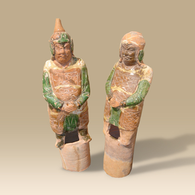 An extremely rare pair of Ming Dynasty green amber-glazed Pottery Attendants